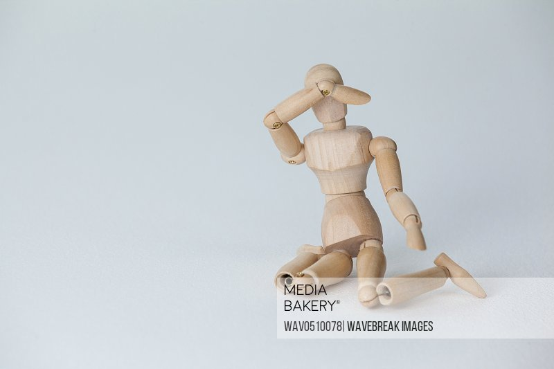 Wooden figurine sitting with hand on head against white background