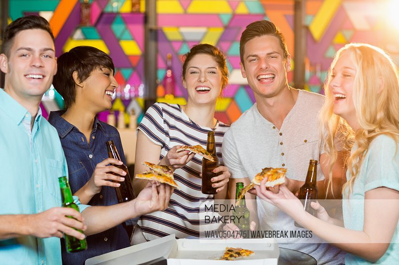 Group of smiling friends having bottle of beer and pizza in party at bar