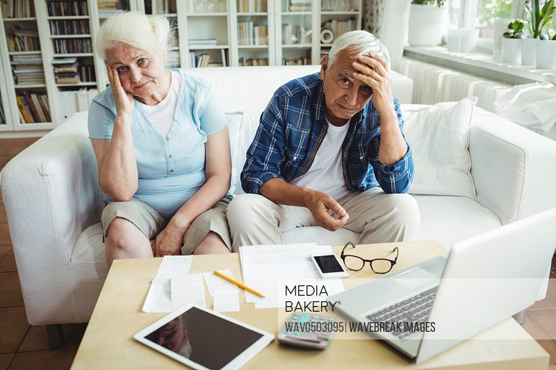 Worried senior couple sitting on sofa at home