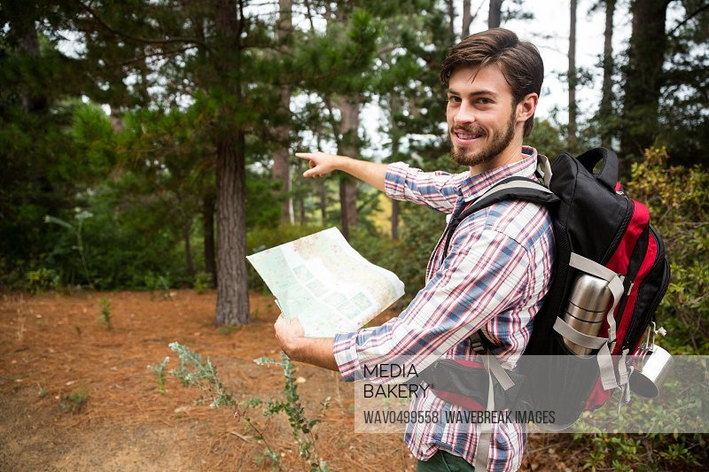 Portrait of male hiker holding a map and showing direction in forest