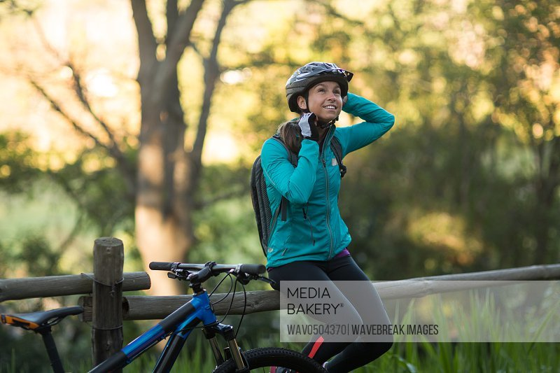 Female biker sitting on a fence and removing bicycle helmet in countryside