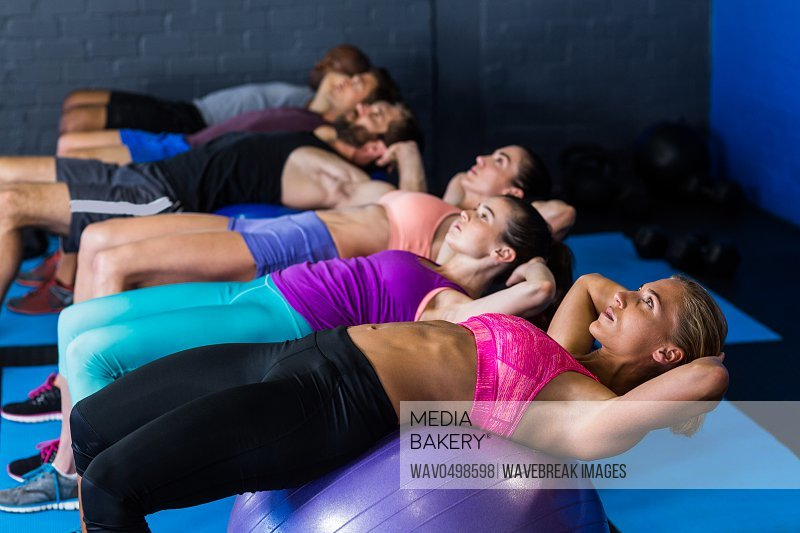 Male and female athletes exercising on fitness ball in gym