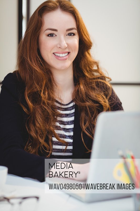 Portrait of happy beautiful young businesswoman using laptop at creative office