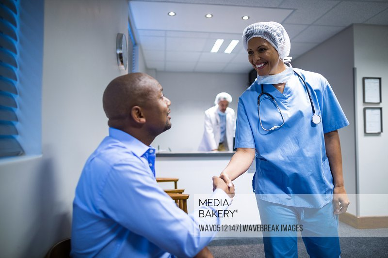 Female doctor shaking hands with patient in hospital