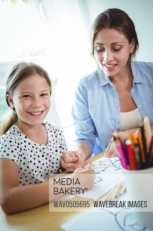 Smiling mother and daughter drawing together at home