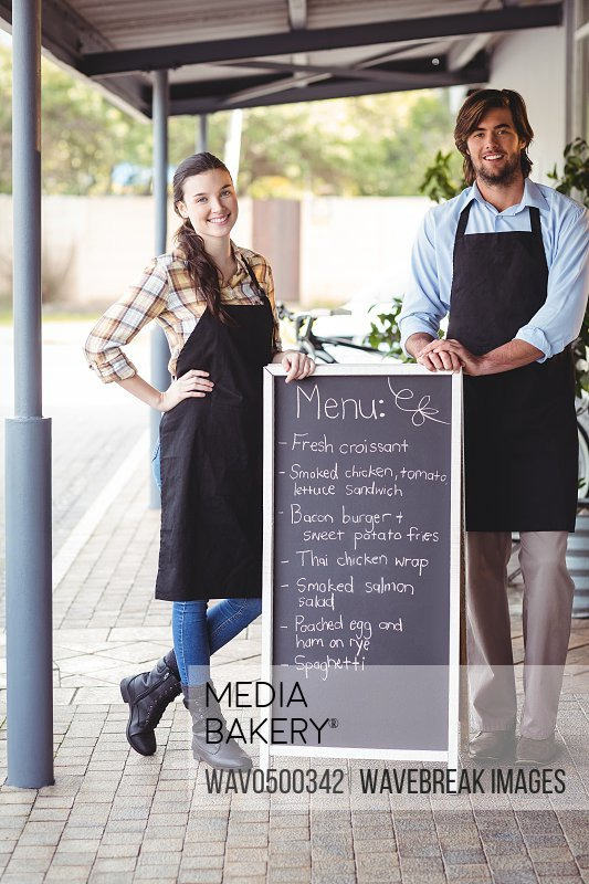 Smiling waiter and waitress standing with menu board outside the cafe