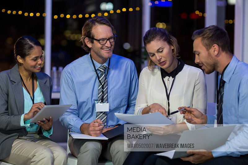 Businesswoman discussing with colleagues over document in office at night