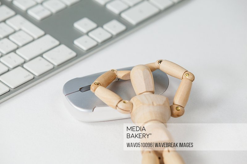 Wooden figurine leaning on mouse beside a keyboard against white background