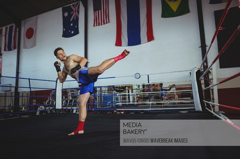 Confident boxer practicing a boxing in boxing ring
