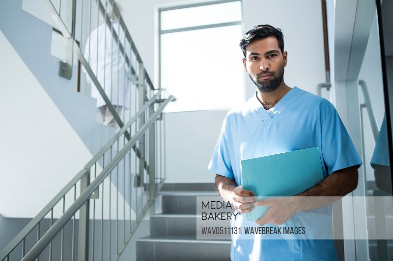 Doctor standing with file on staircase in hospital