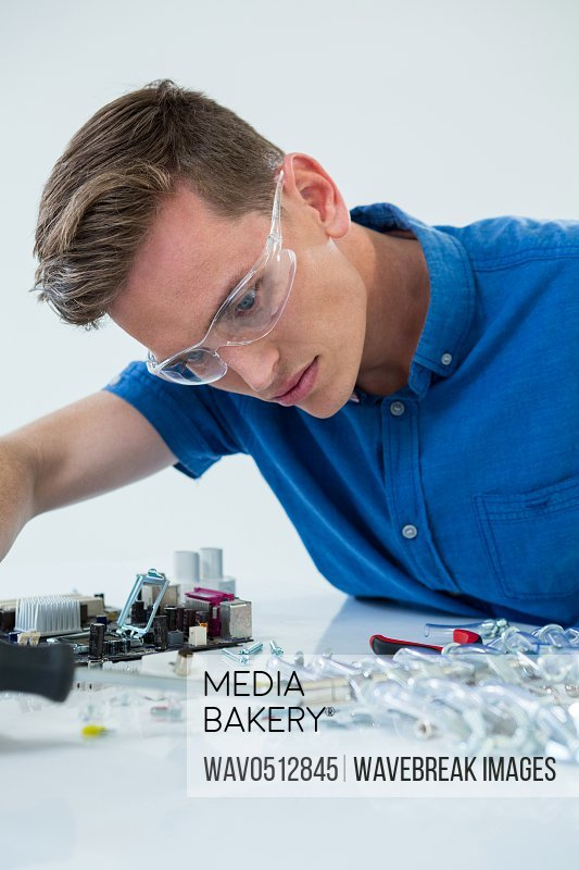 Computer engineer repairing computer motherboard against white background