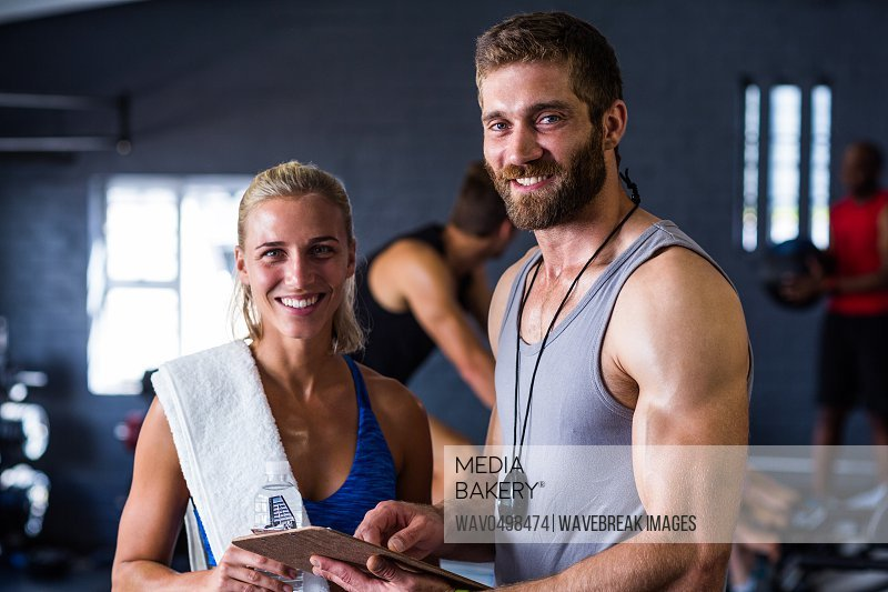 Portrait of smiling fitness instructor with woman standing in gym