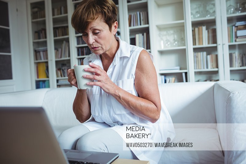Senior woman having a cup of coffee while using laptop in living room
