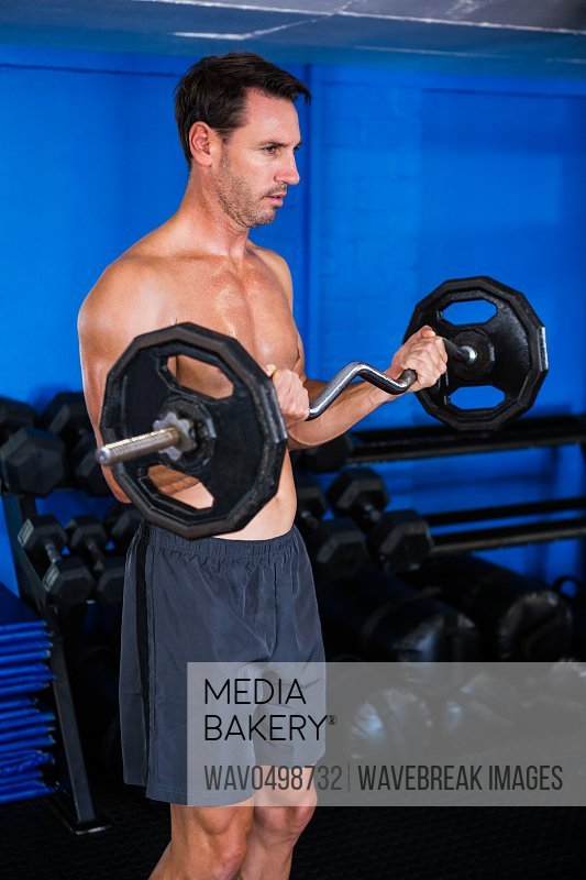 Shirtless athlete holding barbell in gym