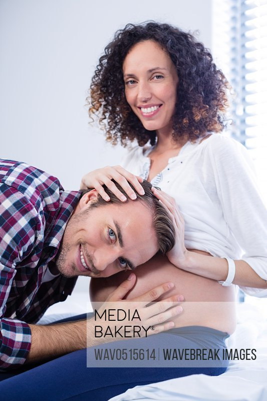 Smiling man listening to pregnant womans belly in ward