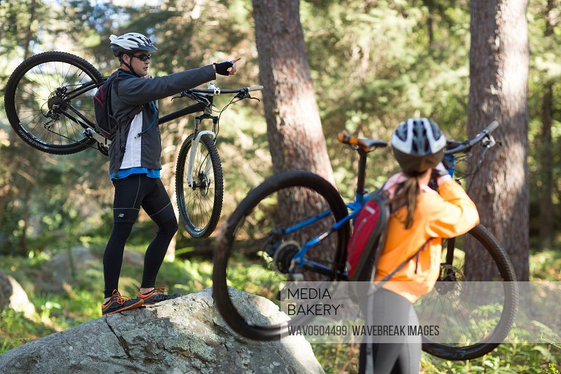 Biker couple holding their mountain bike and pointing at distance in forest