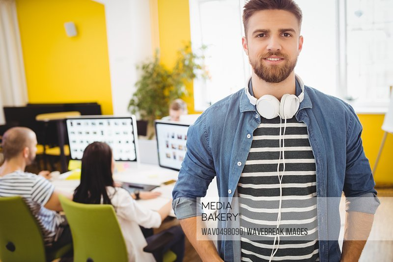Portrait of confident young male executive standing at creative office