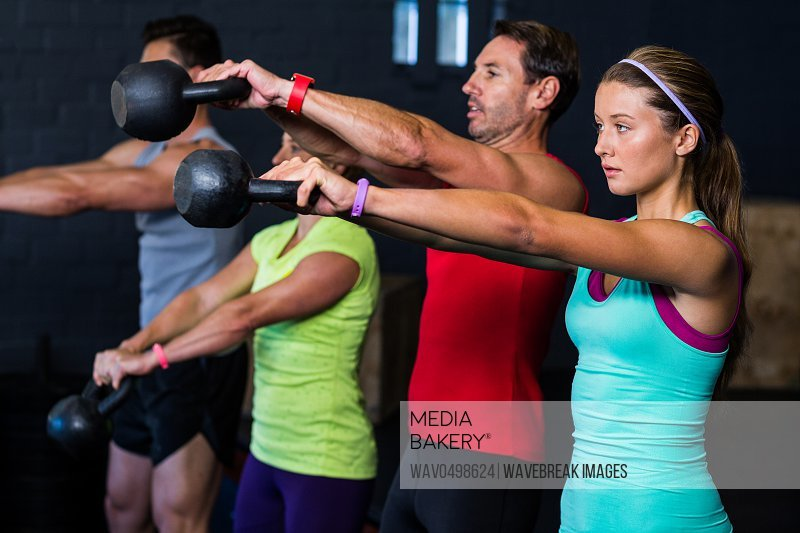 Male and female athletes exercising with kettlebells in gym