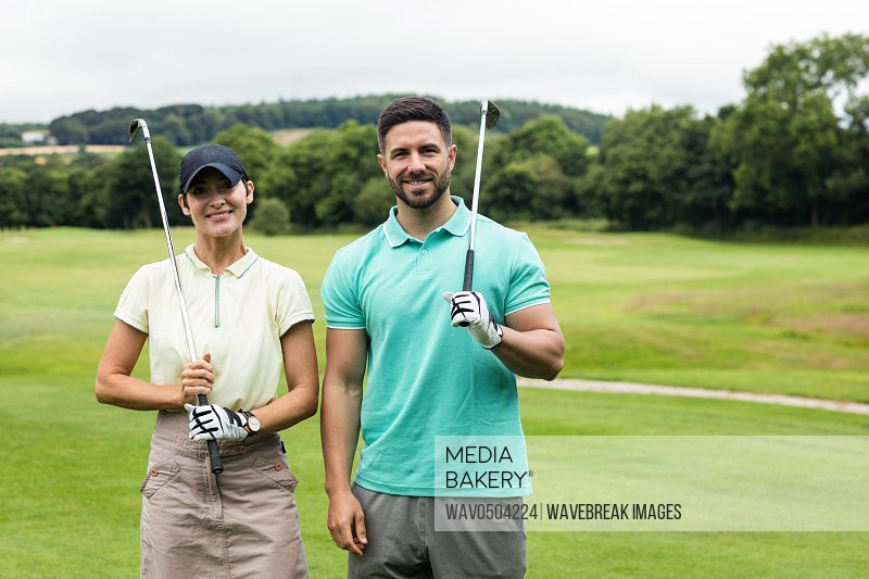 Portrait of smiling couple standing with golf club in golf course