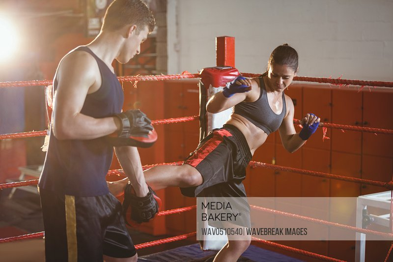 Female boxer practicing kickboxing with trainer her trainer at fitness studio
