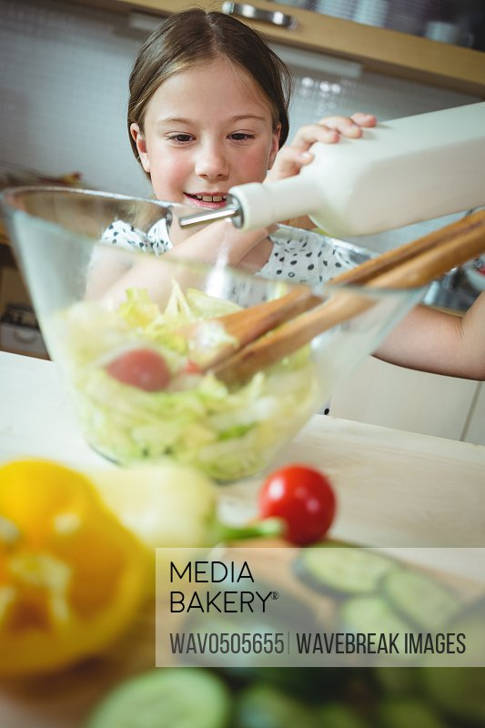 Girl preparing a bowl of salad in kitchen at home