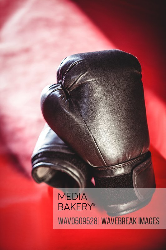 Pair of black boxing gloves on red surface