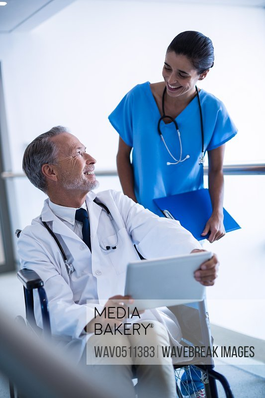 Doctor and nurse discussing over digital tablet in hospital