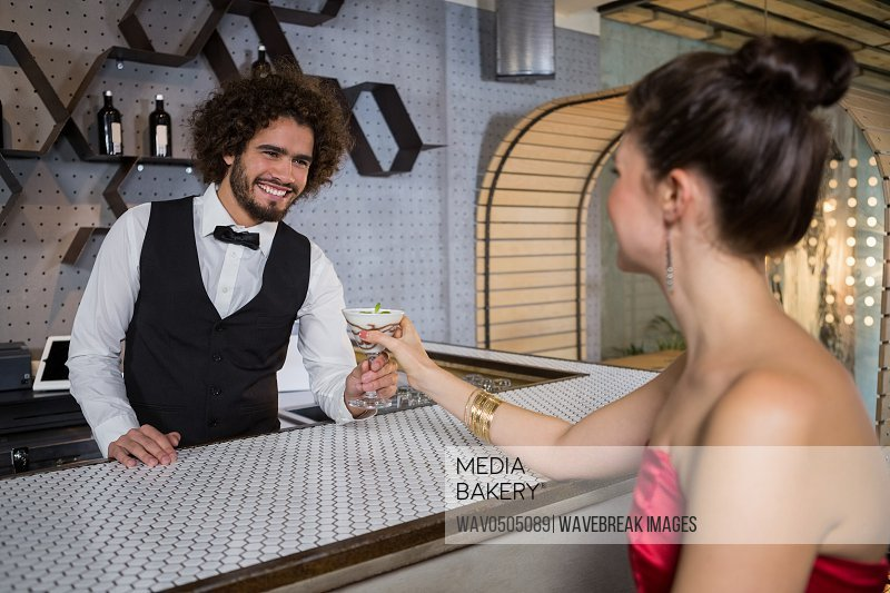 Waiter serving a cocktail to woman at bar counter in bar