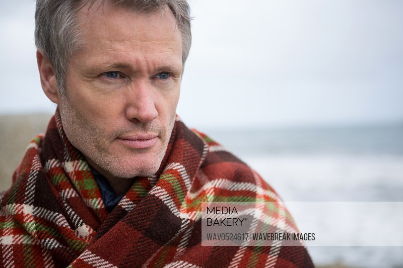 Thoughtful man wrapped in shawl at the beach