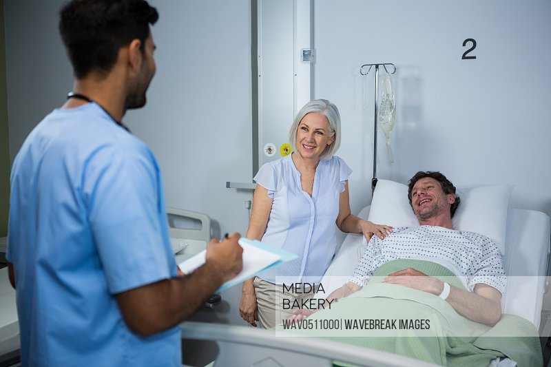 Smiling doctors interacting with each other while patient lying on bed