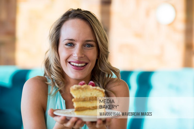 Excited woman holding pastry on plate in cafe