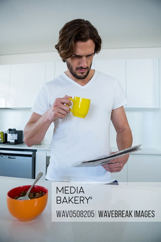 Man reading newspaper while having coffee in kitchen at home