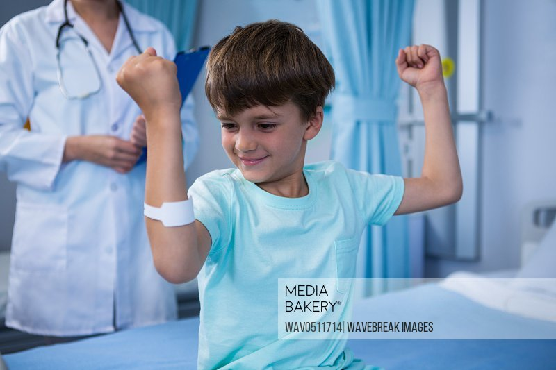 Boy flexing his muscles and female doctor standing in background in ward