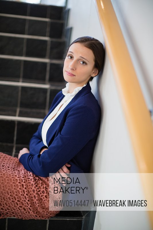 Worried businesswoman sitting on steps