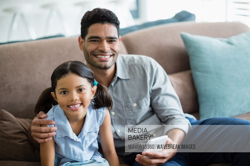 Portrait of father and daughter sitting on sofa in living room