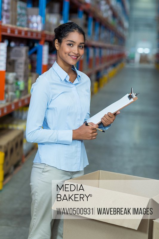 Portrait of female warehouse worker standing with clipboard in warehouse