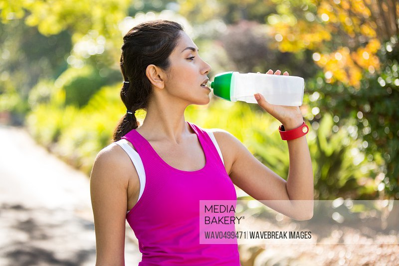 Tired jogger drinking water while taking a break in park