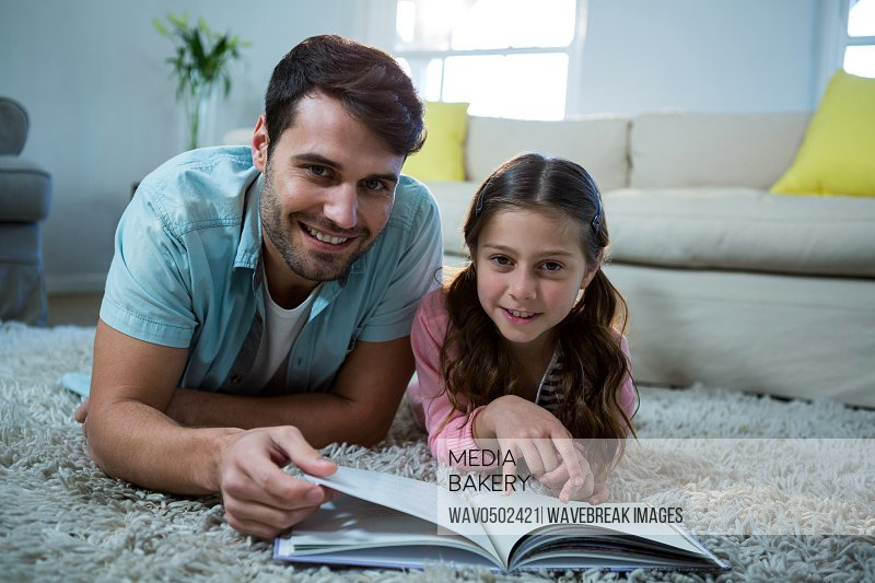 Portrait of father and daughter reading book in the living room at home