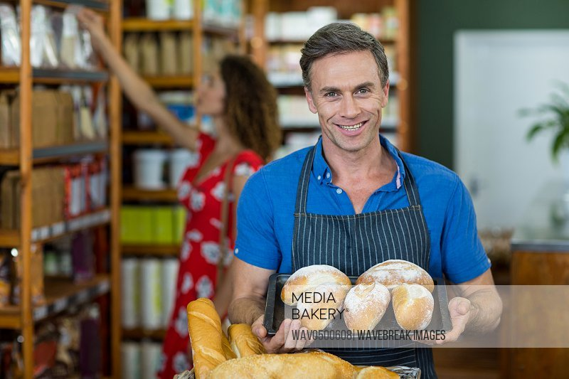 Portrait of male staff holding a tray of bread in supermarket
