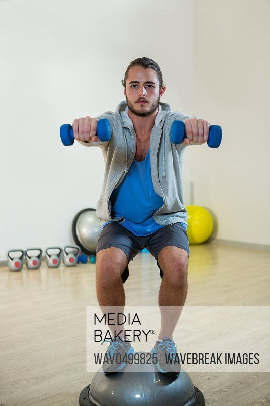 Man exercising with dumbbells on bosuball in gym