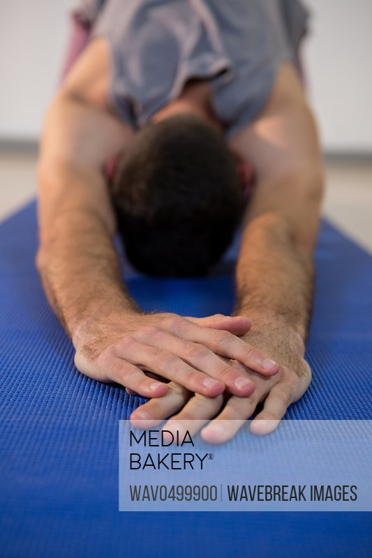 Close-up of man performing yoga in gym