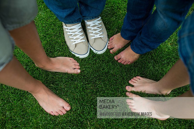 Family standing on grass in park on a sunny day