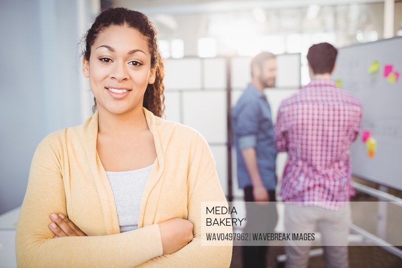 Portrait of confident young businesswoman standing with arms crossed at creative office