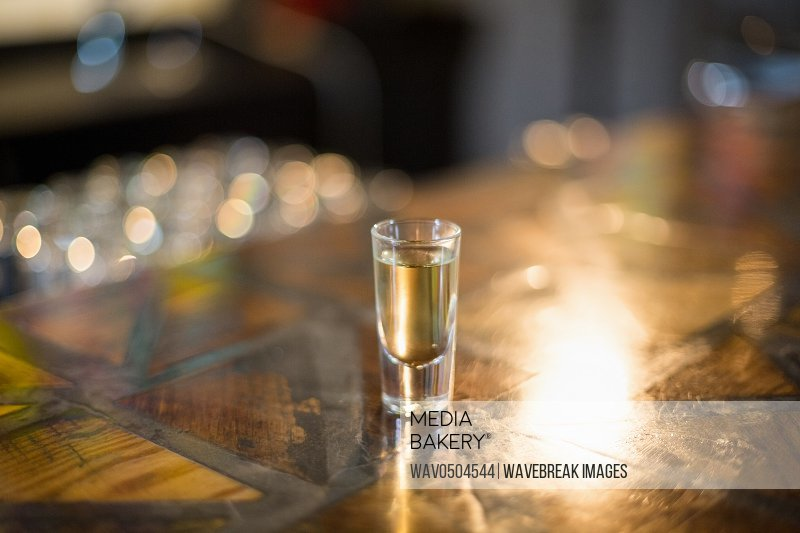 Tequila shot glass on counter at bar