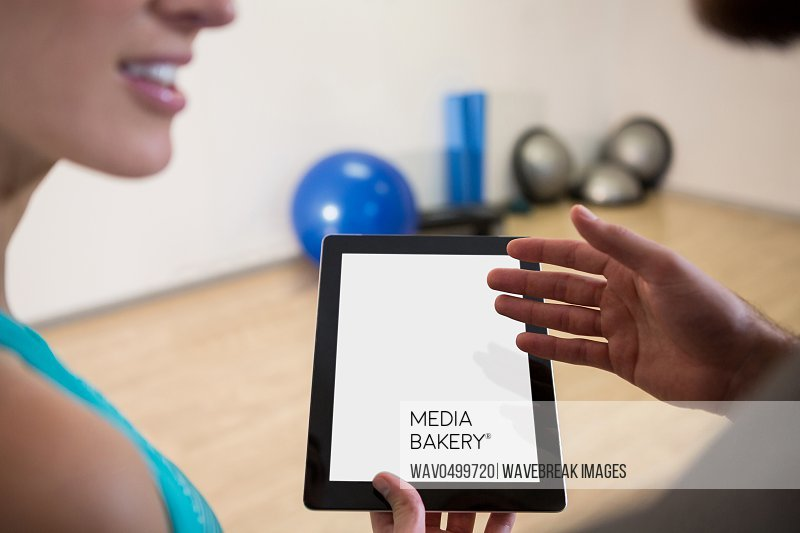 Fitness trainer showing digital tablet to woman in fitness studio