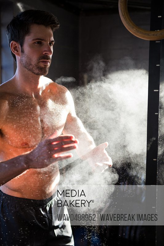 Shirtless male athlete clapping hands with sports chalk in gym