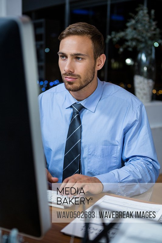 Business executive working on computer in office at night