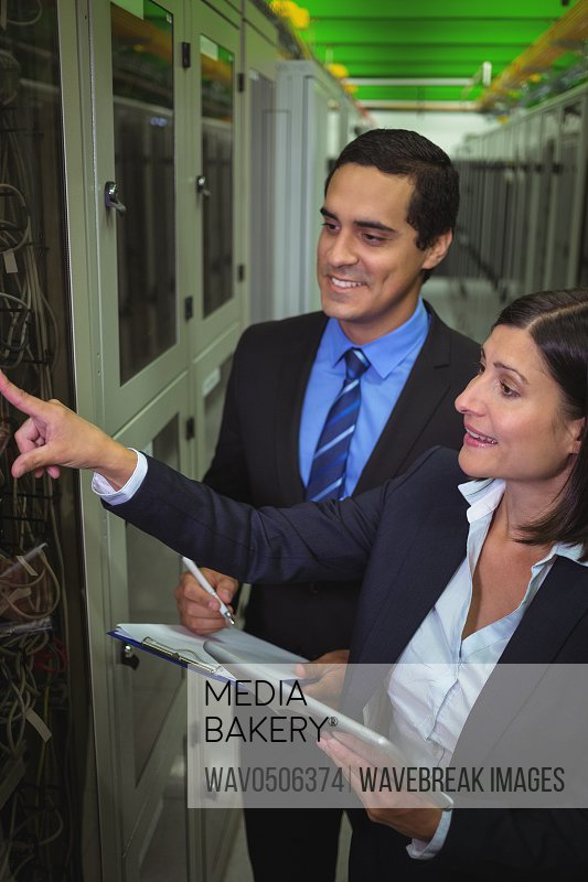 Technicians interacting with each other while analyzing server in server room