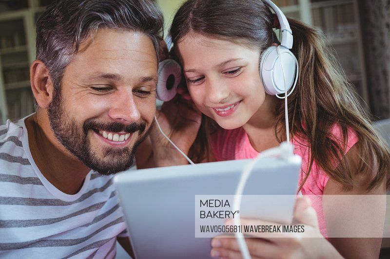 Father and daughter listening music on digital tablet at home