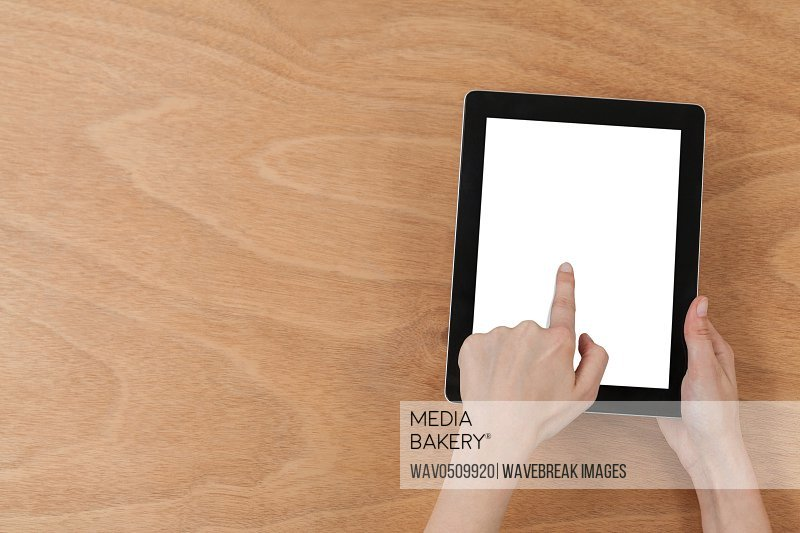 Close-up of hands using digital tablet against wooden background